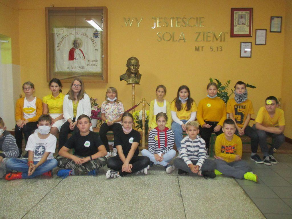 Grupa dzieci pozuje do zdjęcia na tle popiersia i obrazu Jana Pawła 2.